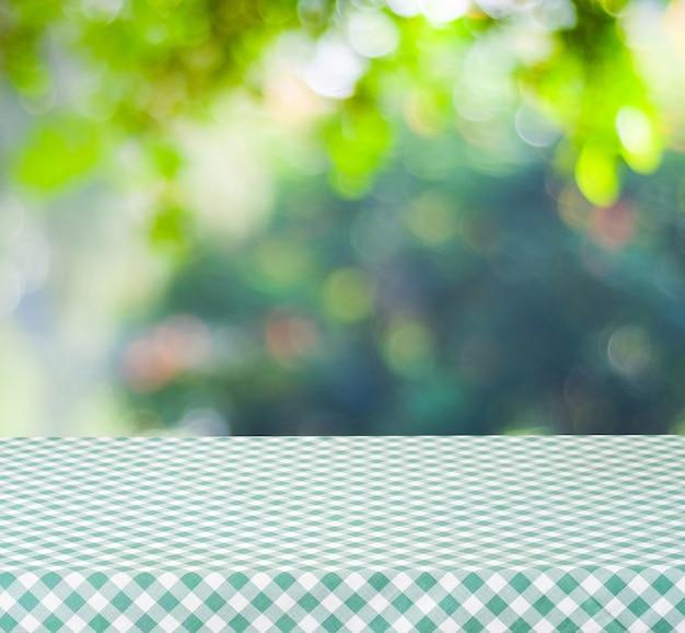 Leeren sie tabelle mit grüner tischdecke über unschärfegarten und bokeh hintergrund