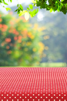 Leeren sie tabelle mit roter tischdecke über unschärfegarten und bokeh hintergrund