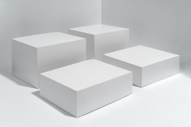 Leeren sie vier weiße plattformwürfel auf weißem hintergrund