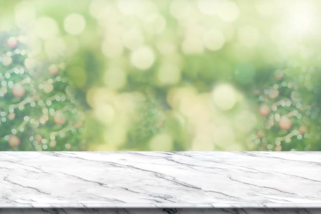 Leeren sie weiße marmortabelle mit unschärfenweihnachtsbaumhintergrund