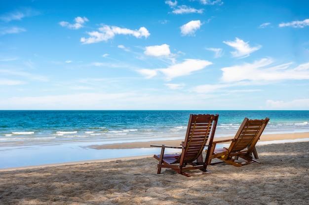 Leeren sie zwei holzstühle am strand im tropischen meer an sonnigen tagen. sommer- und urlaubskonzept
