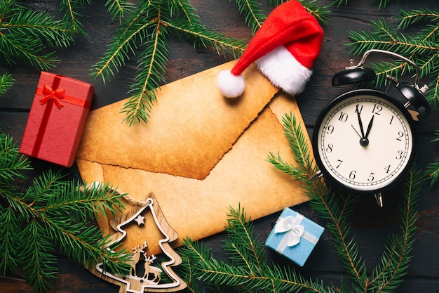 Leerer alter briefumschlag mit weihnachtstannenzweigen mit vintage-wecker, geschenkboxen, hirsch und weihnachtsmütze.