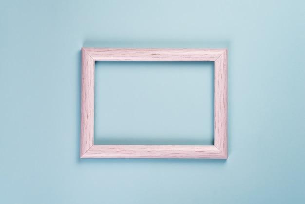 Leerer alter holzrahmen für fotos oder verschiedene bilder auf einem pastellblauen hintergrund.