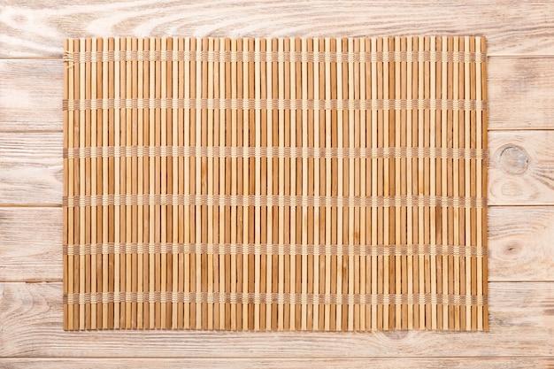 Leerer asiatischer nahrungsmittelhintergrund. braune bambusmatte auf draufsicht des hölzernen hintergrundes mit kopienraumebenenlage