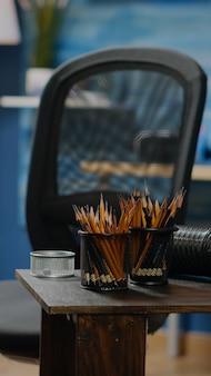 Leerer atelierraum mit bunten bleistiften und vase zum zeichnen. niemand im kreativitätsraum, aber kunstwerkzeuge, hölzerne staffelei, bastelausrüstung für künstlerisches design und meisterwerk