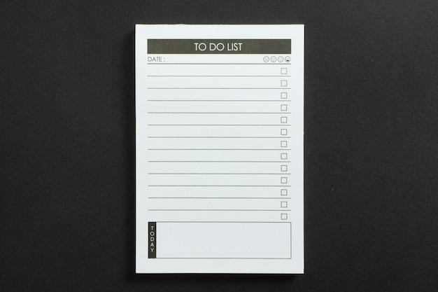 Leerer aufgabenlistenplaner mit checkliste für häkchen auf schwarz strukturiertem hintergrund