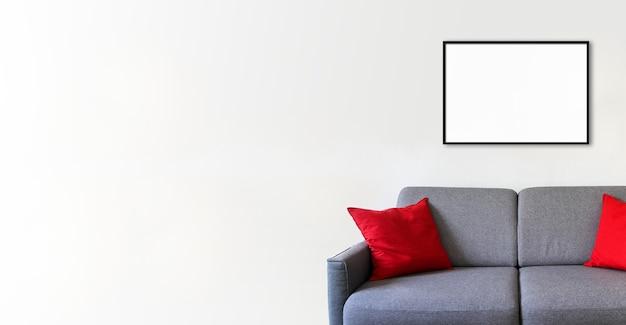 Leerer bilderrahmen an einer weißen wand über einem sofa. minimalistischer innenhintergrund. horizontales banner