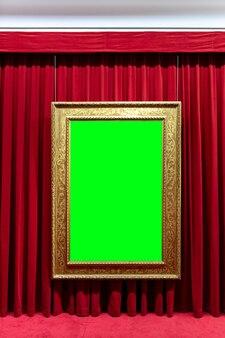 Leerer bilderrahmen auf rotem stoffhintergrund.