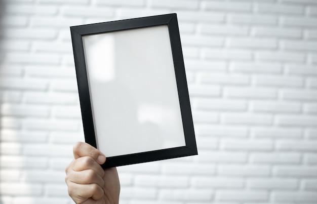 Leerer bilderrahmen auf weißer backsteinmauer.