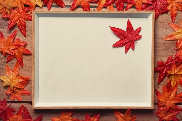 Leerer bilderrahmen mit herbstahornblättern auf hölzernem hintergrund.