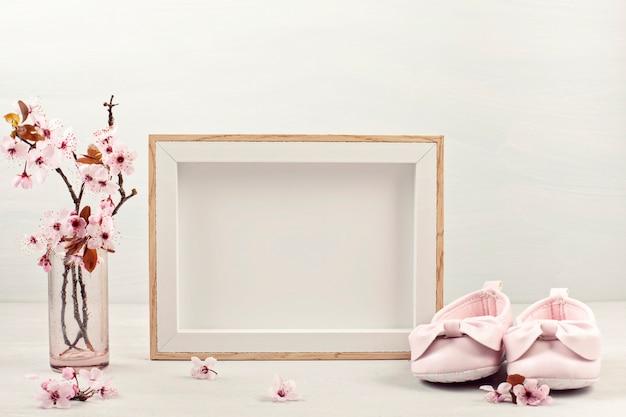 Leerer bilderrahmen, rosa zarte frühlingsblumen und kleine babyschuhe