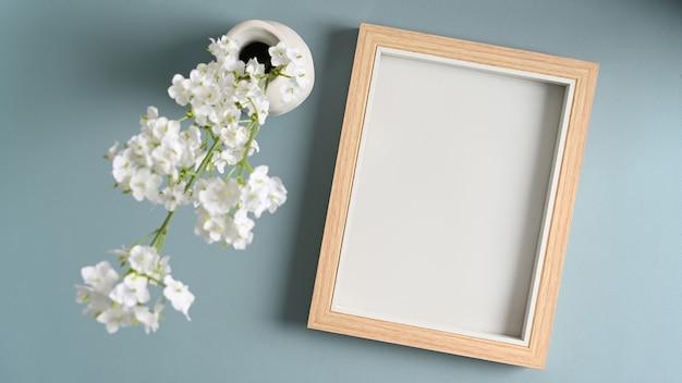 Leerer bilderrahmen und blumen in vasen auf blauem pastenhintergrund.