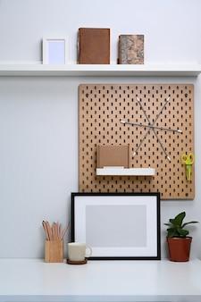 Leerer bilderrahmen und bürobedarf auf weißem tisch im home office.