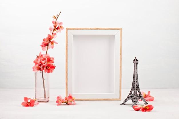 Leerer bilderrahmen und rosa frühlingsblumen.