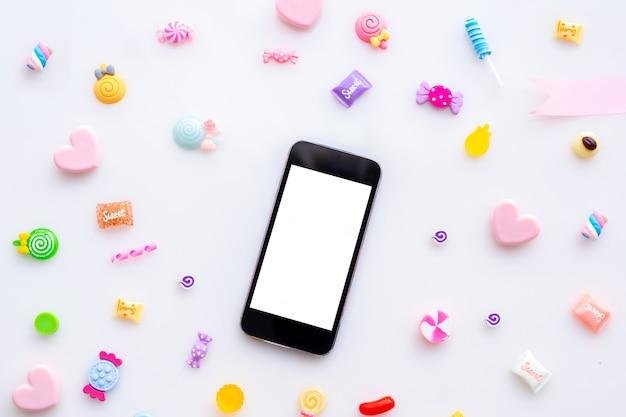 Leerer bildschirm am smartphone-handy, tablette mit süßer süßigkeit auf weißem hintergrund.