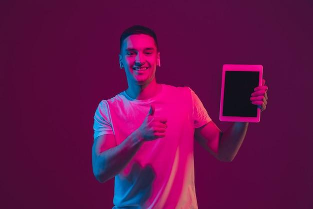 Leerer bildschirm anzeigen. porträt des kaukasischen mannes isoliert auf rosa-violetter wand im neonlicht. männliches model mit geräten. konzept der menschlichen emotionen, gesichtsausdruck, copyspace.
