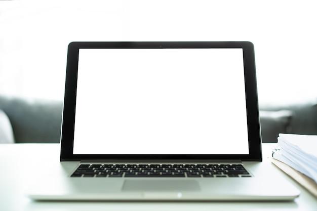 Leerer bildschirm auf einem modernen laptop-computer auf dem weißen tisch im heimbüro hautnah, verspotten den laptop-bildschirm einzeln in weiß mit beschneidungspfad.