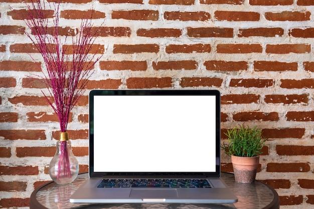 Leerer bildschirm der laptop-computers auf tabelle mit wand des roten backsteins