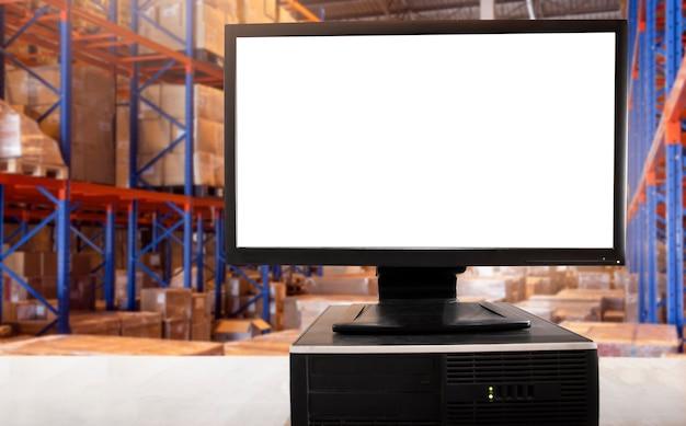 Leerer bildschirm des desktop-computers auf dem tisch in der lagerhaltung.