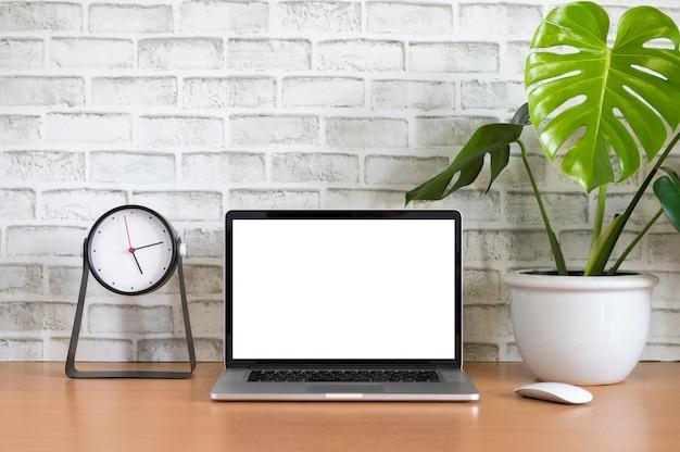 Leerer bildschirm des laptop-computers mit uhr, tablette, handy, maus und monstera-blumentopf auf holztisch