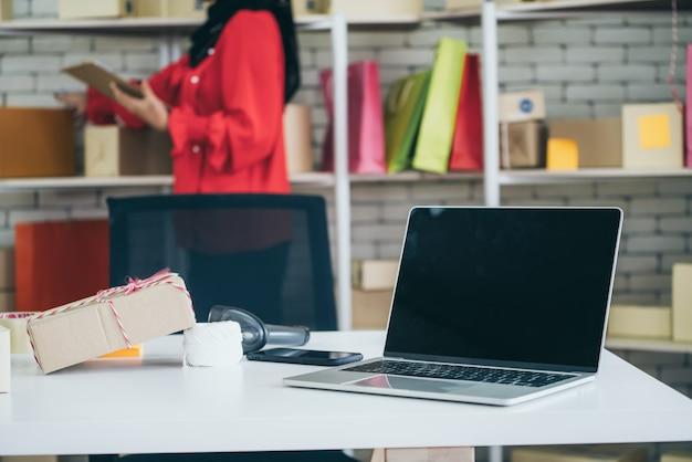 Leerer bildschirm des laptop-computers mit versandkarton im hintergrund