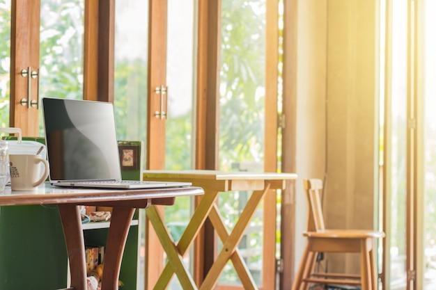 Leerer bildschirm des laptops auf hölzernem schreibtisch und stuhl im rauminnenraum mit morgenlicht