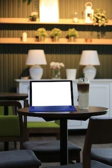 Leerer bildschirm des laptops und kalte kaffeetasse gesetzt auf eine lebensmitteltabelle in einer kaffeestube.