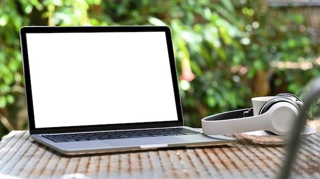 Leerer bildschirm des mockup-laptops und kopfhörer mit kaffeetasse auf eisentisch, grüner baumhintergrund.