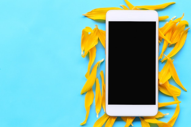 Leerer bildschirm des smartphone der schwarzen farbe gesetzt auf ein blaues papier.