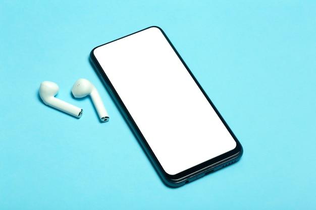 Leerer bildschirm des smartphones auf einem farbigen hintergrund mit kopfhörern. hochwertiges foto