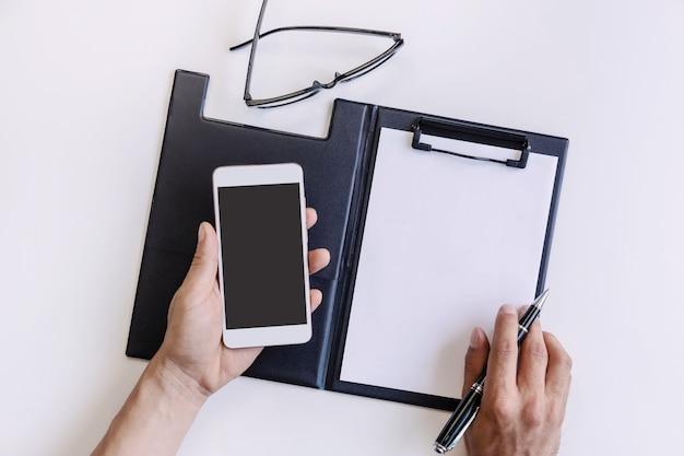 Leerer bildschirm intelligentes telefon und dokument auf geschäftsschreibtischbüro
