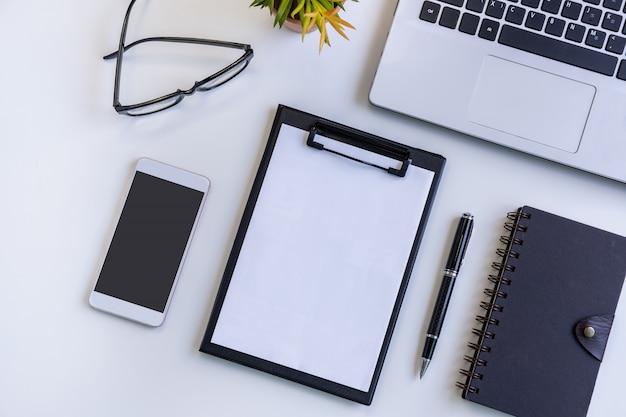 Leerer bildschirm intelligentes telefon und tablette mit laptop auf geschäftsschreibtischbüro mit kopienraum, draufsicht