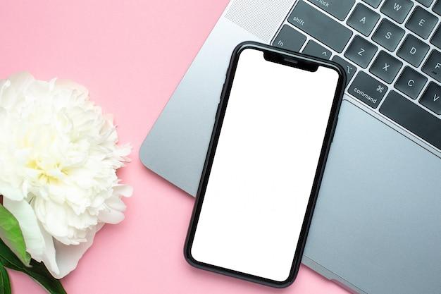Leerer bildschirm, laaptop und blume des handys auf rosa mit kopienraum