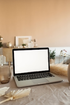 Leerer bildschirm laptop auf tisch mit schönen dekorationen. modernes, gemütliches, komfortables wohnzimmer-innendesign.