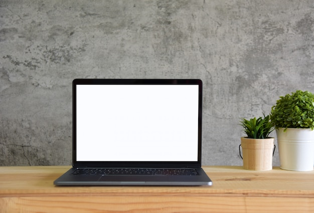 Leerer bildschirm laptop-computer auf arbeitstisch vorderansicht im loft-raum-stil