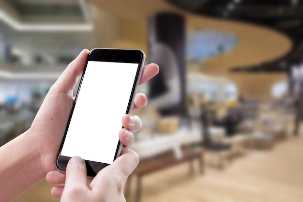 Leerer bildschirm smartphone in der frau überreicht unscharfen hintergrund bei holel.