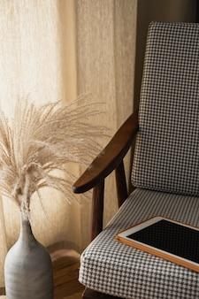 Leerer bildschirm-tablet-pad auf retro-stuhl mit pampasgras-bouquet. arbeitsplatz im homeoffice