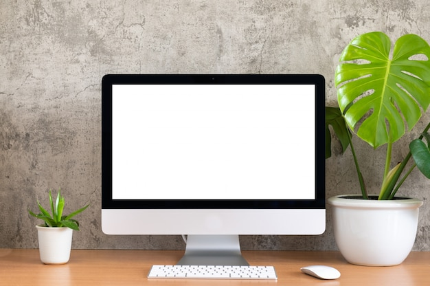 Leerer bildschirm von all in einem computer, tastatur, maus, monstera-topf und kleinem blumentopf auf holztisch
