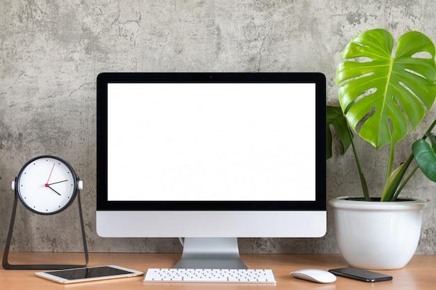 Leerer bildschirm von all in one computer, tastatur, maus, tablet, telefon, monstera blumentopf und uhr auf holztisch