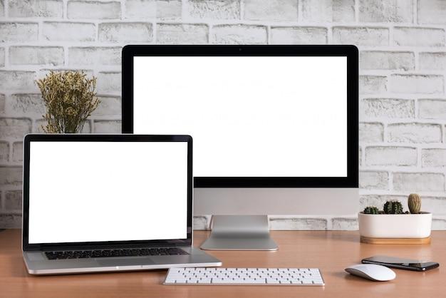 Leerer bildschirm von allen in einem computer und in einer laptop-computer mit intelligentem telefon- und kaktusvase