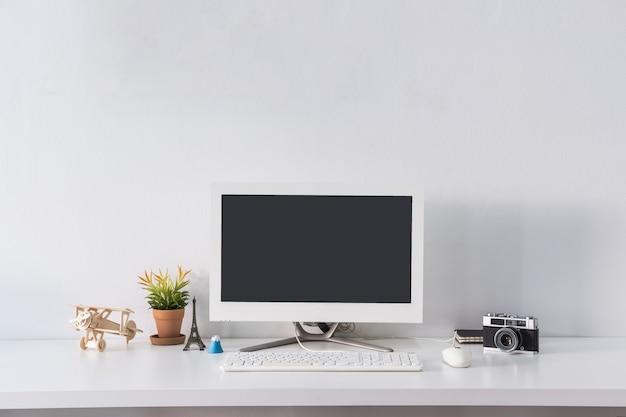 Leerer bildschirmcomputermonitor auf schreibtischbüro mit retro- kamera