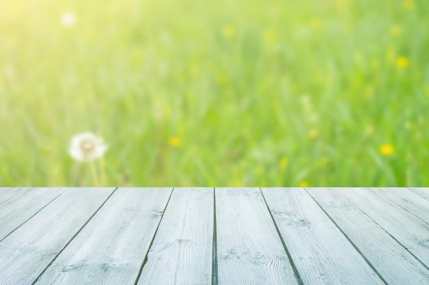 Leerer blauer holztisch mit unscharfem stadtpark auf hintergrund. konzeptparty, produkte, sommerhintergrund