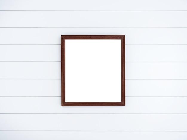 Leerer brauner quadratischer hölzerner bilderrahmen auf sauberer weißer hölzerner plankenwand.
