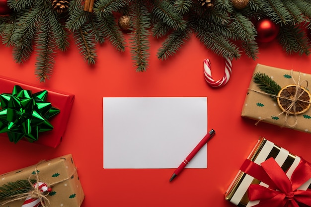 Leerer brief auf rotem hintergrund mit geschenken und weihnachtsdekoration