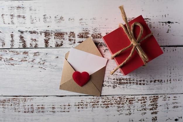 Leerer buchstabe auf hölzernem hintergrund, valentinstagkonzept