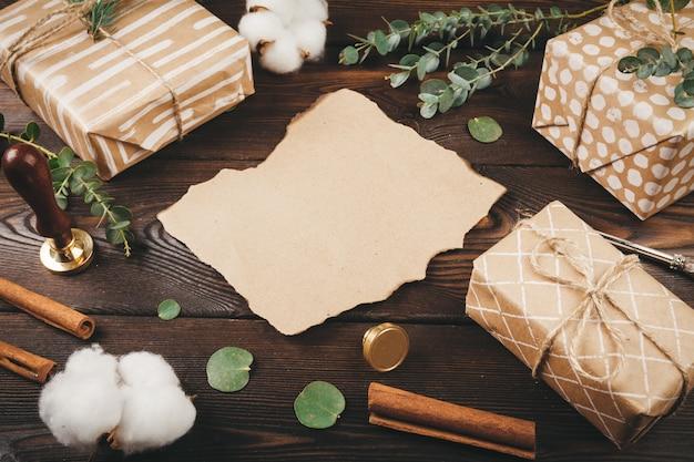 Leerer buchstabe mit einer feder auf dem alten hölzernen hintergrund verziert mit weihnachtsgegenständen