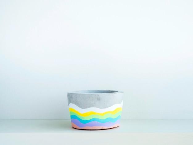 Leerer bunter diy runder betontopf auf einem weißen holzregal auf weißer wand mit kopienraum. einzigartiger regenbogenfarben lackierter zementübertopf.