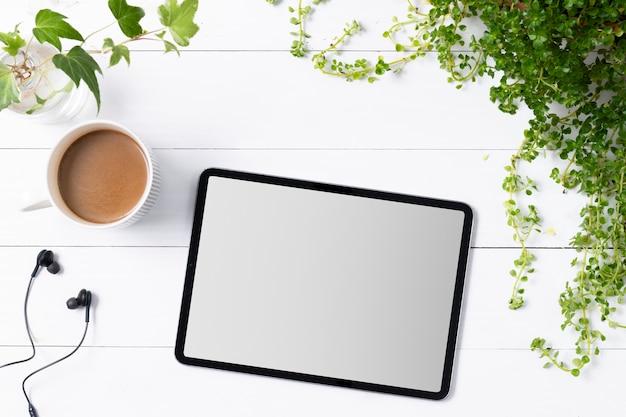 Leerer digitaler tablet-bildschirm im zimmerpflanzenhintergrund