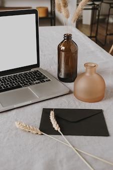 Leerer display-laptop, umschlag, flauschige pflanzen, roggen- / weizenohrstiele, dekorationen auf grau gewaschenem leinentuch