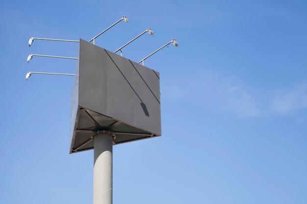 Leerer dreieckiger anschlagtafelpfosten mit lichtern gegen blauen himmel